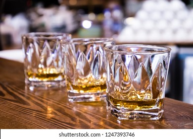 three glasses of whisky on the wooden bar