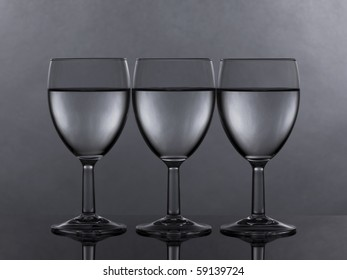 three glasses of white wine or water filled to the same level