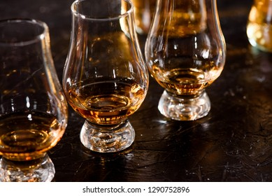 Three Glencairn Glass with whiskey on a bar wooden counter close up on the background of blurry bottles. Close up. Dark background