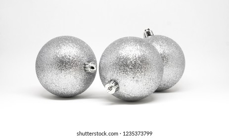Three glittering silver Christmas tree decorative balls isolated on a white background