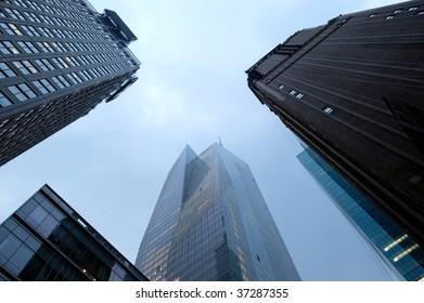 three gloomy skyscrapers against rainy sky in NY, US