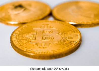 three gold coins bitcoins, lying on a white background