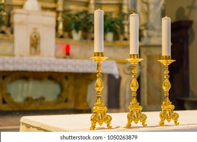 Three golden candelabra lined up on the church altar.