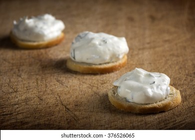 Three golden crackers with cream cheese over wooden background