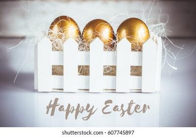 Three golden easter eggs on white background