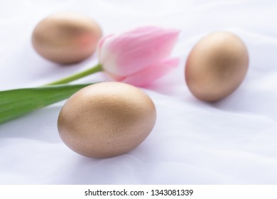 Three golden Easter eggs and pink tulip laying on white fresh linen