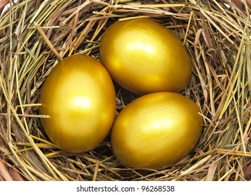 Three golden eggs in the hay nest