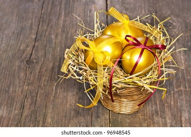 Three golden eggs in the hay nest on wooden table