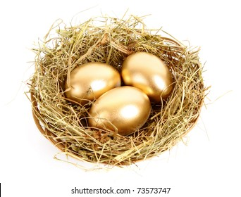 Three golden hen's eggs in the grassy nest isolated on white