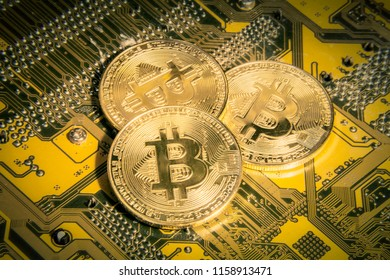 Three golden physical bitcoins resting on a printed circuit board. Yellow and orange tones. Close-up shot.