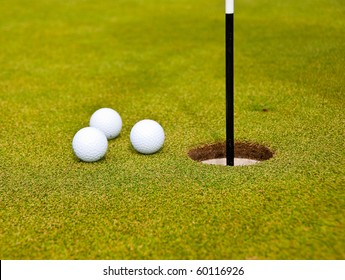 Three golf balls on green with flag. Shallow depth of field. Focus on the closest balls and the hole.