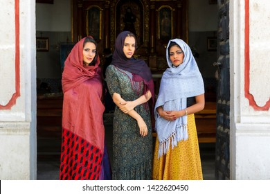 Three gorgeous Hispanic Brunette models pose outdoors in a Catholic Church environment