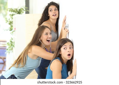 Three gossip girls listening through the neighbour wall at home