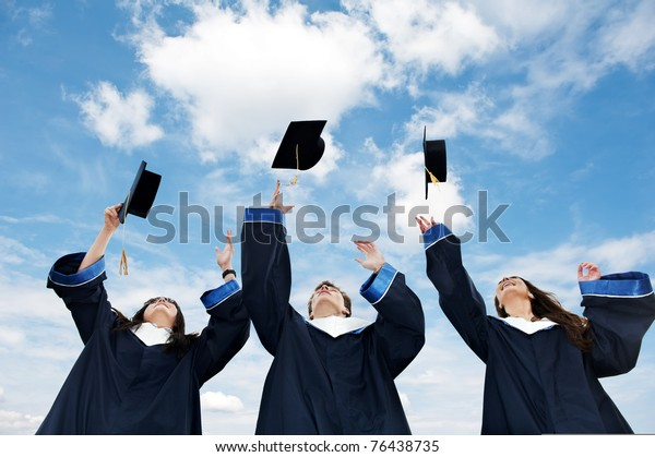 drei Absolventen, die Hüte über den blauen Himmel hochwerfen