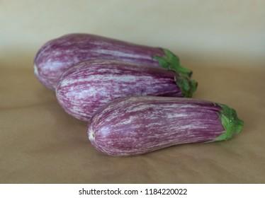 Three graffitti eggplants on baking sheet background