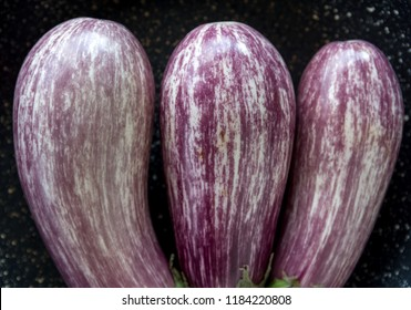 Three graffitti eggplants on black background