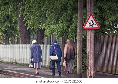 Three grandmothers walking on a street on a rainy spring day at Tallinn, the capital of Estonia. The traffic sign above them warns about running children.