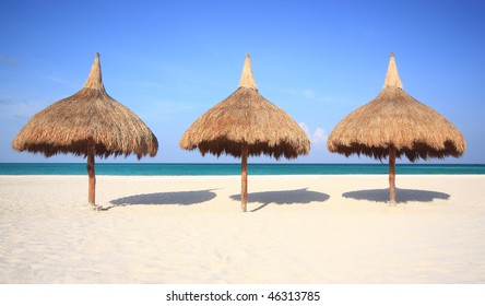 Three grass umbrellas on a resort beach