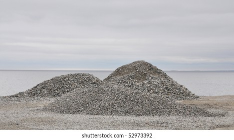 Three gravel piles by the sea.