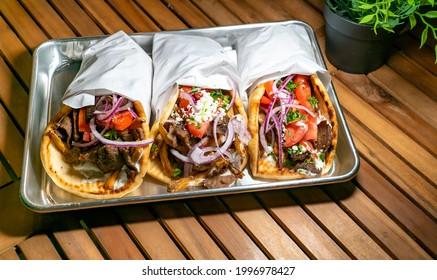 Three Greek Gyros on a Plate: Lamb, Tzatziki Sauce, and Veggies