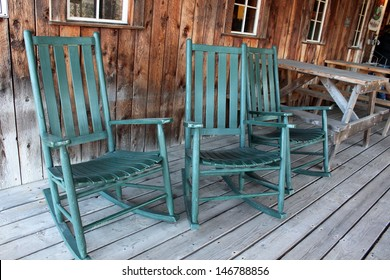 Three green Adirondack rocking chairs on old wood porch seem to welcome visitors to come and sit a spell in the middle of their busy day.