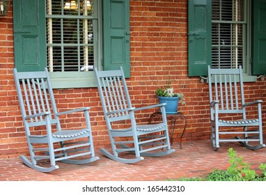 Three green Adirondack rocking chairs sit under rural country brick-front home with shuttered windows on old, weathered front porch invite friends and family to come sit awhile.