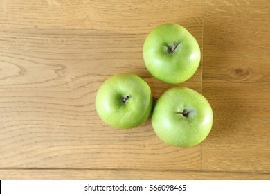 Three green apple isolated on a wooden background.