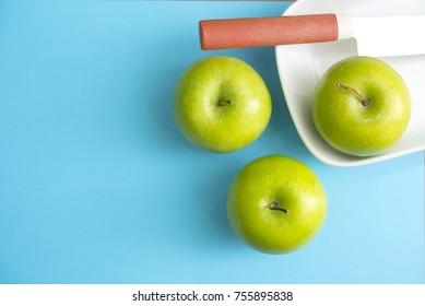 three Green apple on blue background with knife to cut. flat lay out,top view