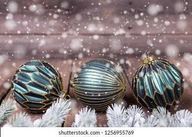 Three  green  balls on vintage wooden  background. Decorative christmas composition. Selective focus.  Drawn snow. Place for text.