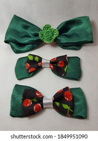 Three green Christmas satin fabric handmade decorating bows. Also can be used as hair accessories. The largest bow is to the top. The others are decorated with a hit of red cherries.