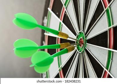 Three green darts pinned on the center of dartboard
