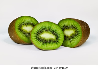 Three green kiwi fruit in a cut on a white background