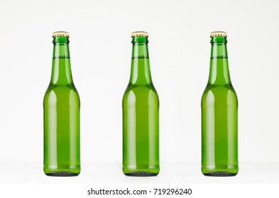 Three green longneck beer bottles 330ml, mock up. Template for advertising, design, branding identity on white wood table.