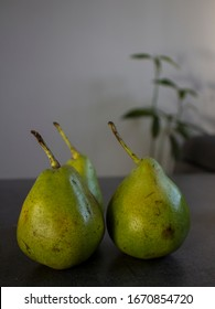 Three green pears on dark grey table. White background.