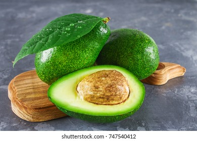 Three green raw ripe avocado fruits and a cut half with a bone with leaves on a wooden cutting board on a gray dark concrete table.