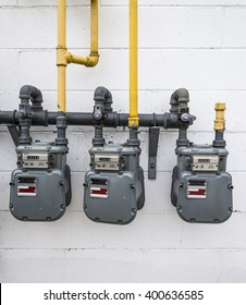 Three grey gas meters hang on a white brick wall.