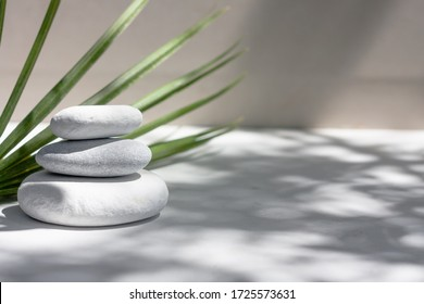 Three grey roundstones and bath towels on white background with green leaves. Spa stones, zen like concept.