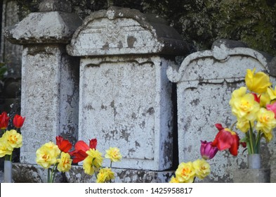 Three grey stones of differing height stand together as part of a shrine. They are marked with age and covered with moss. Yellow daffodils and red poppies have been placed before them.