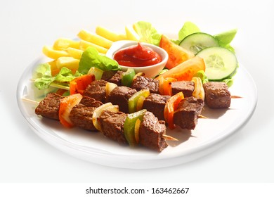Three grilled beef and sweet pepper kebabs served on a plain white plate with french fries, tomato ketchup and mixed salad on a white background