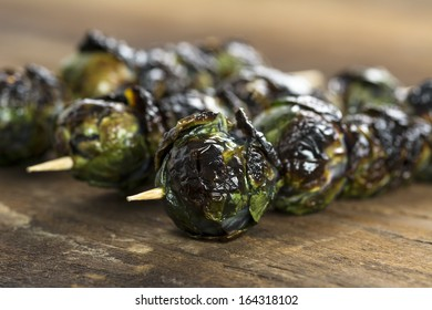 Three grilled organic purple Brussels sprouts on skewers set on wood