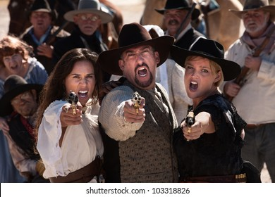 Three gunfighters yell while shooting in outdoor old west scene
