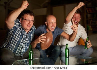 Three guys cheering in front of TV while watching american football game