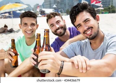 Three guys drinking beer at  beach