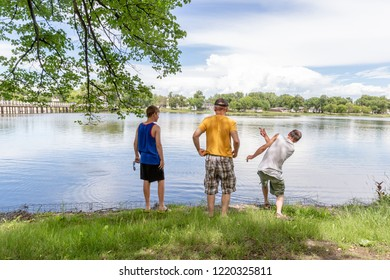 three guys standing by the water in the park spending quality ti
