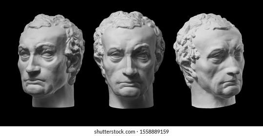 Three gypsum copy of ancient statue Gattamelata, Erasmo di Narni, head isolated on black background. Plaster sculpture man face.