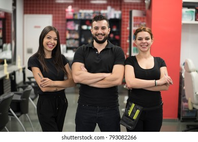 Three hairdressers posing in barber shop