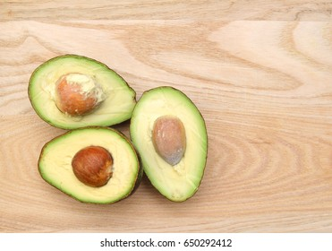 Three half avocado isolated on wooden board