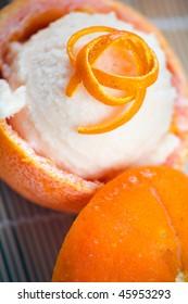 Three hallowed oranges filled with fresh italian orange sorbet on a japanese towel.