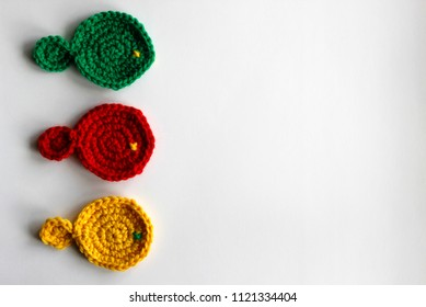 Three hand made knitted fish isolated on white background with copy space. Red, green and yellow children toys in one row. Flat layout representing concept of team going together in the same direction