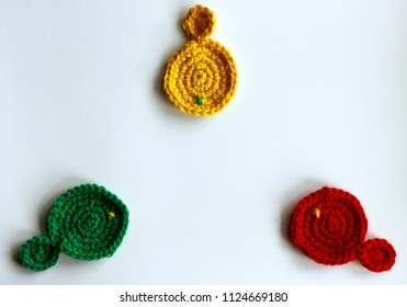 Three hand made knitted fish isolated on white background. Red, green and yellow circle facing each other. Flat lay representing concept of conference, meeting, discussion, compromise or agreement.
